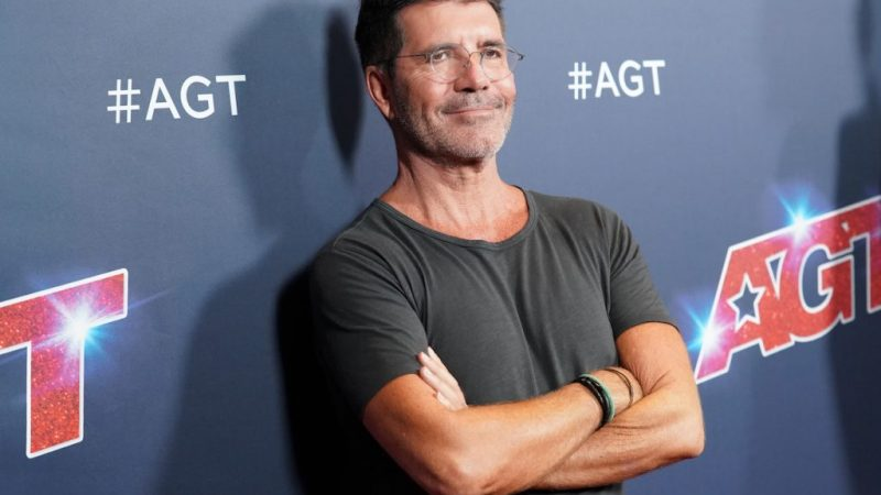 Simon Cowell smiling with arms crossed
